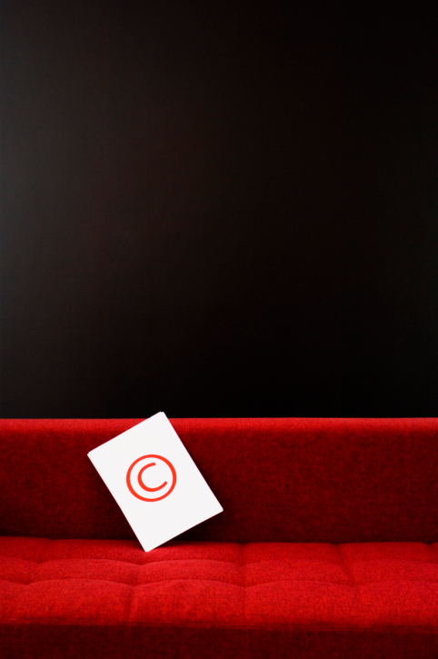 Copyright icon sitting on a red couch