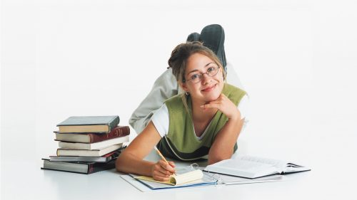 Young Smiling Woman Studying with Books Surrounding Her